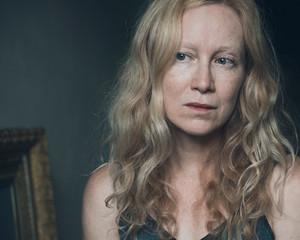 e294b86bef102 Woman with long reddish blonde wavy hair looking away