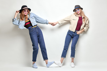 Wall Mural - Two Playful Sisters Having Fun in in Stylish Autumn Outfit. Young lovable Hipster Girl in Fashion denim jacket, Trendy hat. Blond Redhead Woman Smiling, Happy positive emotion