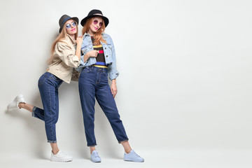 Wall Mural - Two Playful Friends Having Fun in Studio. Young Beautiful Hipster Girl in Stylish jacket, jeans. Autumn Fashion Trendy Outfit. Full-length portrait woman, Happy positive emotion