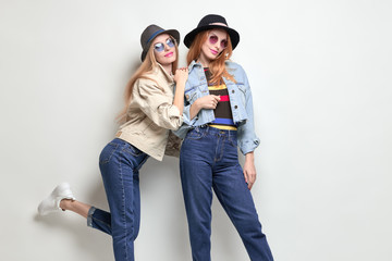Wall Mural - Two Playful Friends Having Fun in Studio. Young Beautiful Hipster Girl in Stylish jacket, jeans. Autumn Fashion Trendy Outfit. Blond Redhead Woman Smiling, Happy positive emotion