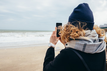 Candid photo of hipster girl traveler on sand shore at winter