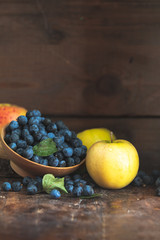 Autumn harvest blue sloe berries and apples on a wooden table background. Dark rustic style