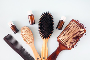 Comb, different types of hair brushes and small, brown glass bottles are pastel blue background. Hair problem and solution. Healthcare concept. Empty place for text or logo.