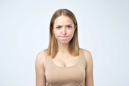 Puzzled woman looking with big opened eyes into camera biting her lips and having some doubts and uncertainty