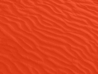 texture of red sand waves on the beach or in the desert. the ripples of the sand is diagonal.