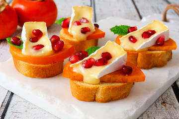 Spoed Fotobehang Voorgerecht Holiday crostini appetizers with persimmons, pomegranates and brie cheese. Close up, side view scene on a bright background.