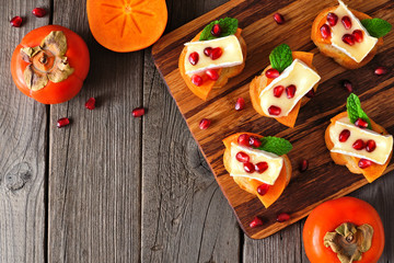 Spoed Fotobehang Voorgerecht Holiday crostini appetizers with persimmons, pomegranates and brie cheese. Top view scene on a wood background.