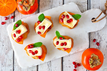 Holiday crostini appetizers with persimmons, pomegranates and brie cheese. Top view scene on a white paddle board.