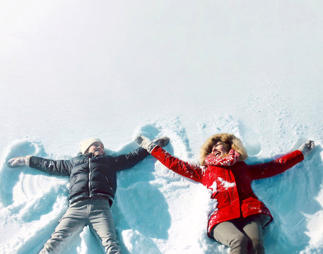 Happy family in winter time! mother with son child lying on snow having fun, making snow angels, blank copy space background