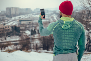 Athletic man taking cityscape photo with phone in winter day