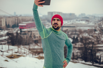 Athletic man taking selfie photo over the city with phone