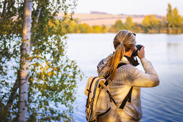 Woman with backpack is photographing a landscape near to lake in golden hour