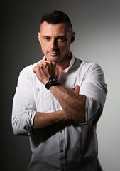 Brutal happy business man thinking in white style shirt on grey dark shadow background. Closeup portrait