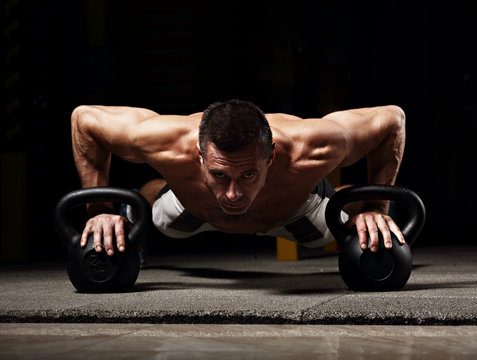 Handsome strong brutal man doing plank on kettlebells, push-up on weights on dark sport club background. Training in light gym on art shadow. Toned contrast portrait