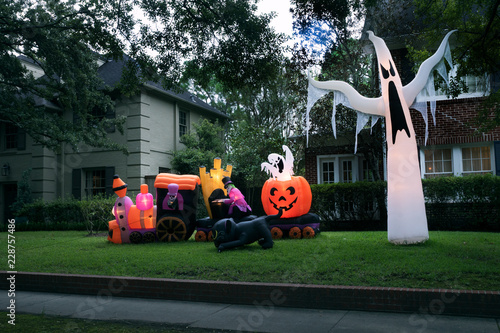The house is decorated for Halloween: Inflatable train with the dead, big pumpkin, black cat huge and small ghost. Night, Houston, Texas, United States