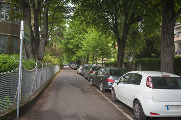 Suburban residential street with modern brick houses and cars parked along the street