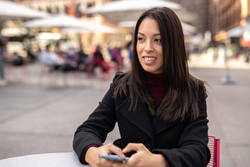 Young woman in city using cell phone using cell phone