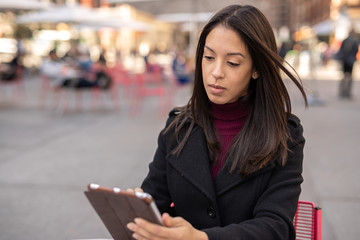 Young woman in city using tablet computer