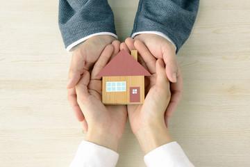 手に包まれた住宅模型