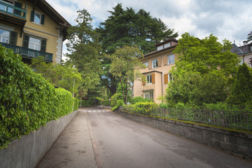 Side view of asphalt road, street in suburban residential area with lot of green trees in Europe is an excellent green and clean country. Environmental and transportation background