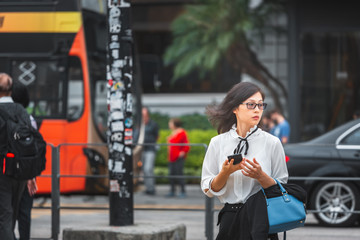 Business woman walking on crowded city street in Hong Kong