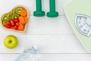 Diet and weight loss for healthy care with  weight scale and fitness equipment,fresh water and fruit healthy, green apple, banana, carrot on white wooden background top view.  Healthy Concept..