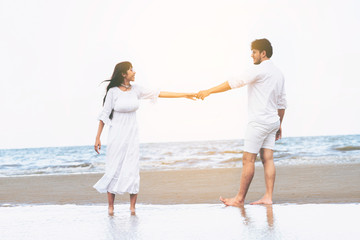 Couple going honeymoon on tropical beach in summer