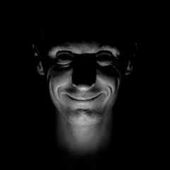 Stylish portrait of adult caucasian man with kind smile. Black and white shot, low-key lighting.