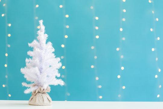 Small white christmas tree on a shiny light blue background