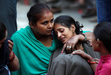 A woman is consoled as she mourns the death of a relative after a commuter train traveling at high speed ran through a crowd of people on the rail tracks in Amritsar