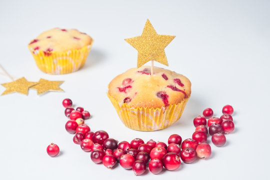 cranberry cupcakes on a white table with a golden star topper