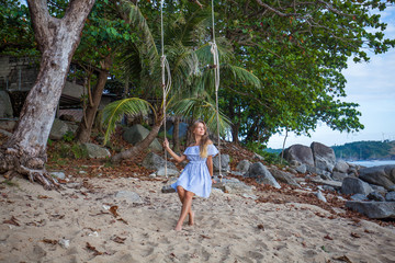 Woman on the swing at the tropical sea shore