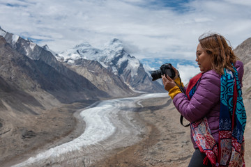 Travelling woman with camera on rang of mountains with snow.