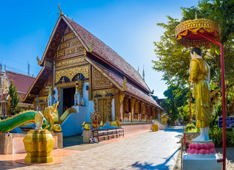 """Wat Phra Singh temple is a buddhist temple located in Chiang Rai, northern Thailand. Landmark of Chiang Rai, Translation text in the image """"Yung tree planted by the monks in the temple"""""""