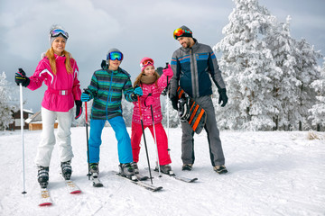 family with ski and snowboard on ski holiday in mountains