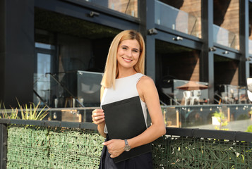 Female real estate agent with clipboard outdoors