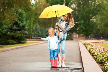 Happy mother and daughter with umbrella under rain in park