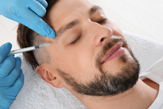 Man getting facial injection in clinic. Cosmetic surgery concept