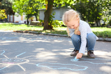 Little child drawing with colorful chalk on asphalt. Space for text