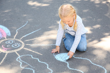 Little child drawing with colorful chalk on asphalt