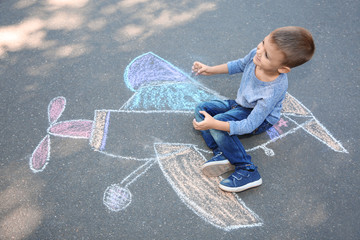 Little child sitting near chalk drawing of airplane on asphalt