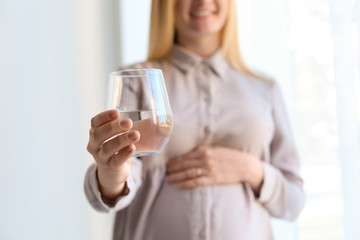 Young pregnant woman with glass of water indoors, closeup