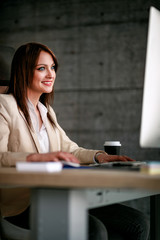 Smiling female designer using computer in office