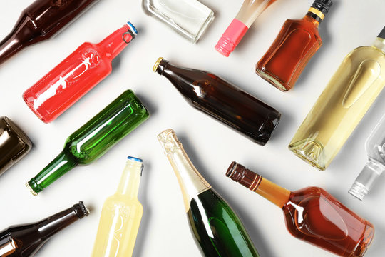 Bottles with different alcoholic drinks on light background, flat lay