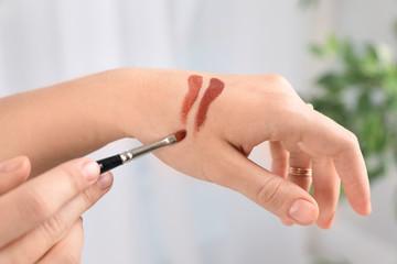 Woman testing and choosing lip gloss color on hand, closeup
