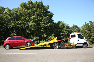 Broken car and tow truck on country road
