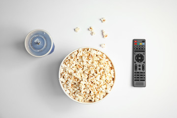 Bucket with popcorn, cup of beverage and TV remote on white background, top view. Watching cinema