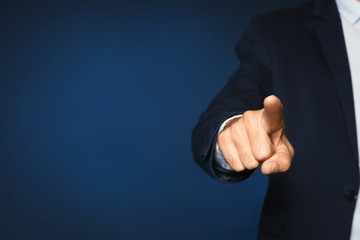 Businessman pointing on color background, closeup view of hand with space for text