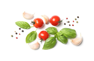 Fresh green basil leaves, cherry tomatoes and garlic on white background, top view