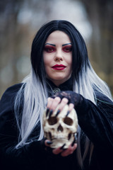 Portrait of witch woman in black cloak with skull